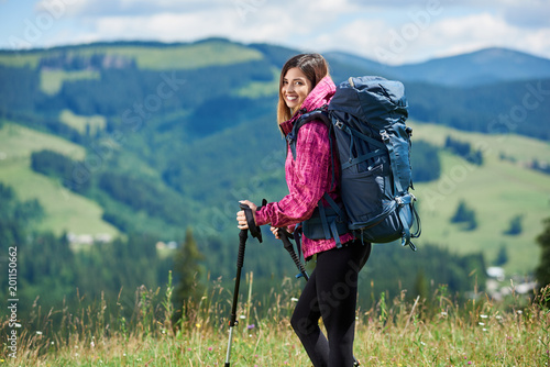 Fototapeta Portrait of beautiful sporty woman hiker with blue backpack and trekking sticks, hiking in the mountains, smiling to the camera, enjoying summer day in the mountains. Concept of active lifestyle obraz