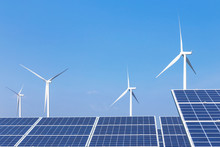 Rows Array Of  Polycrystalline Silicon Solar Panels And Wind Turbines Generating Electricity In Hybrid Power Plant Systems Station With Blue Sky