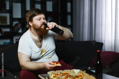 Fotografía  Fat man drinks beer sitting on the sofa and watches TV