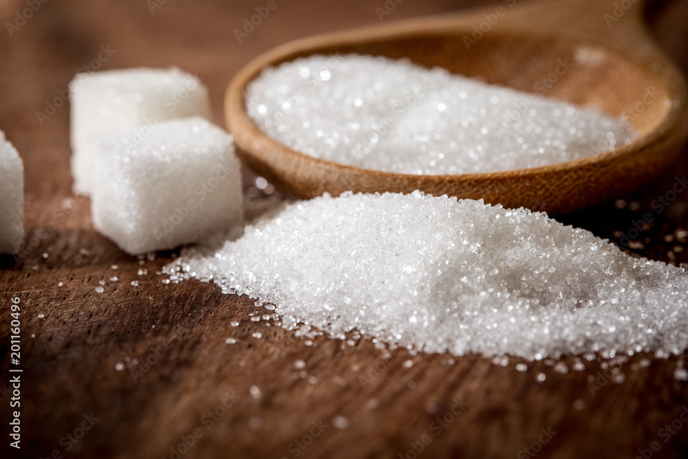 Fototapety, obrazy: Close up a sugar cubes and cane in wooden spoon on the table