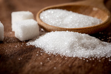 Close Up A Sugar Cubes And Cane In Wooden Spoon On The Table