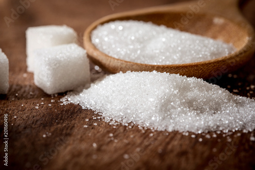 Fototapeta Close up a sugar cubes and cane in wooden spoon on the table