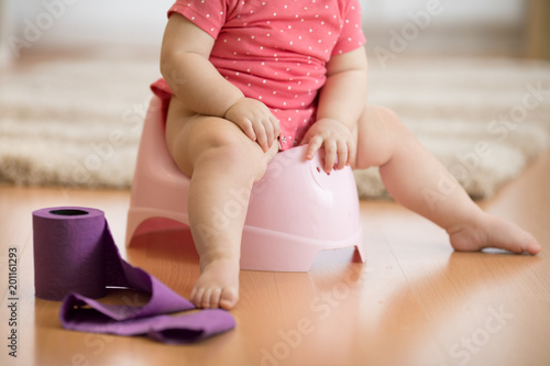 Poster Wintersporten Closeup of legs of one year old baby toddler girl child sitting on potty in nursery room