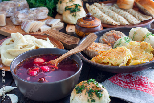 Traditional food in the Ukrainian cuisine - borsch, vareniki, bacon, broth, nalgovniki, cutlets in Kiev, dranniki, pampushki, on a wooden table, selective focus, top view