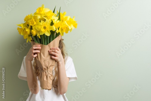 Photo Child girl holding bouquet of yellow flowers.