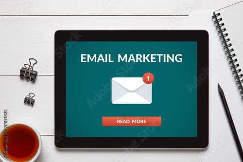 Email marketing concept on tablet screen with office objects on white wooden table. All screen content is designed by me. Flat lay