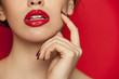 Leinwandbild Motiv red glossy lipstick on red background