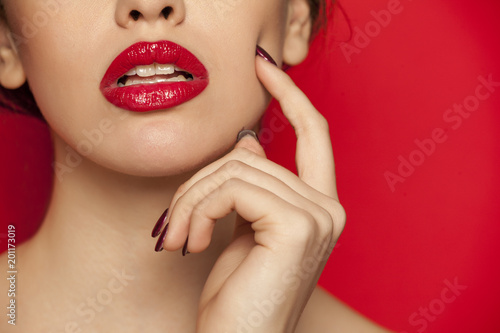 Foto op Canvas Bedehuis red glossy lipstick on red background