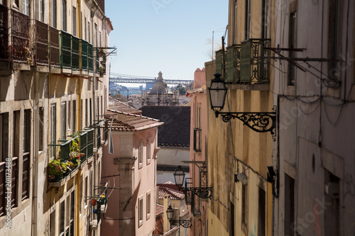 Typical rustic street in Lisbon overlooking the 25 de Abril Bridge