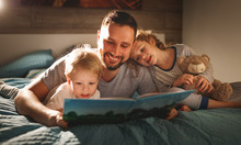 Evening Family Reading. Father Reads Children . Book Before Going To Bed .