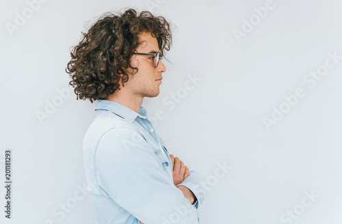 Valokuva  Profile view of handsome young male with curly hair, wearing denim shirt and round spectacles looking to the copy space for advertisement