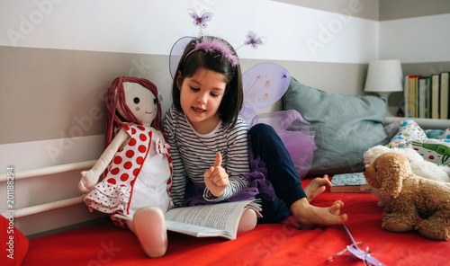 Photo Little girl disguised as a butterfly sitting on the bed reading a book to her ra