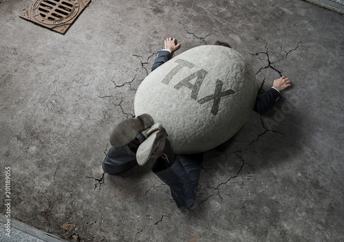 Obraz na plátně  Tax concept, high angle view of businessman crushed by the huge stone on the str