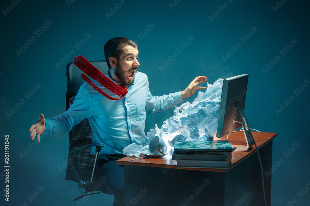 Fototapeta Young stressed handsome businessman working at desk in modern office shouting at laptop screen and being angry about spam