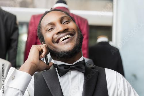 Black elegant man talking on phone and laughing