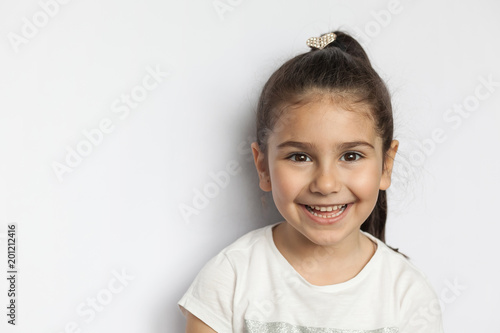 Portrait of happy cute brunette child girl on white background