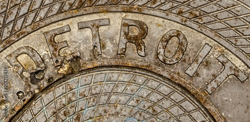 In de dag Donkergrijs Detroit Michigan Background. Rusty manhole cover with the word Detroit engraved on it.