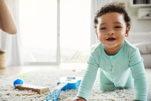 Happy Mixed Race Toddler Boy Crawling In Sitting Room