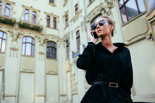 Gorgeous young lady in elegant black coat communicating by cell phone, wearing sunglasses, standing near the old building. Outside.