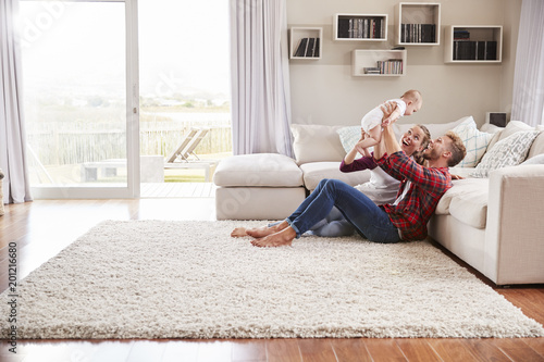 Fotografie, Obraz  Young white couple play with their toddler in sitting room
