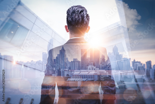 Fotografie, Obraz The double exposure image of the businessman standing back during sunrise overlay with cityscape image