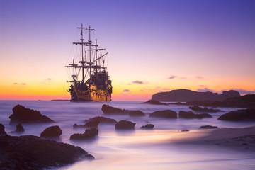 Statek piracki na otwartym morzu o zachodzie słońca