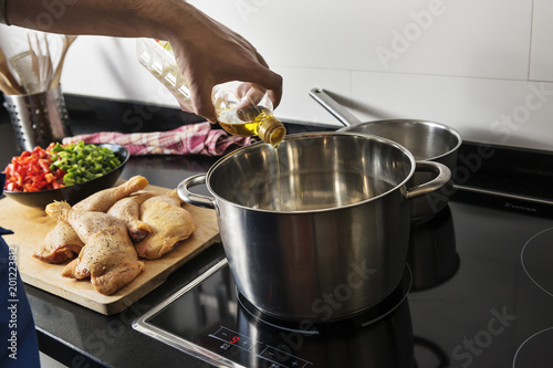 Chef hand pouring oil into a cooking pot