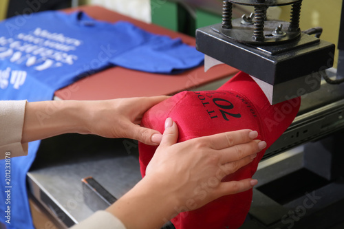 Pinturas sobre lienzo  Young woman printing on cap at workshop
