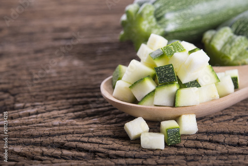 whole and cube cut fresh zucchini on wooden background