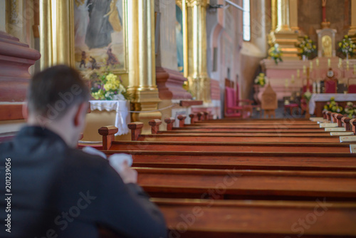 a young man or priest in a black shirt sits on a wooden bench and prays inside t Wallpaper Mural