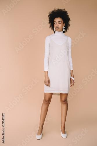 beautiful young woman in stylish white dress on beige Slika na platnu
