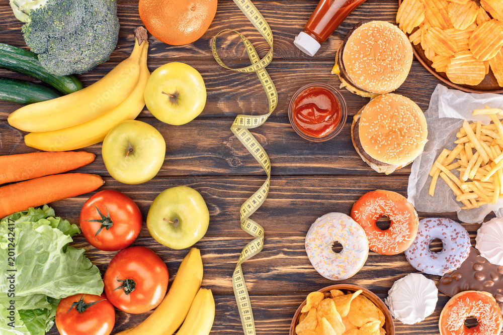 Fototapety, obrazy: top view of assorted junk food, fresh fruits with vegetables and measuring tape on wooden table