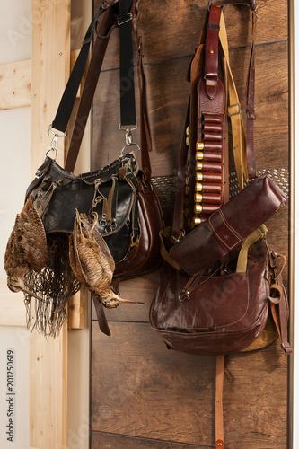 Fényképezés  Hunting trophies and equipment hang on wall