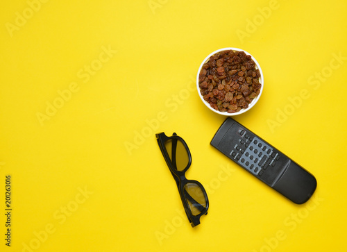 Fotografie, Tablou  3d glasses, tv remote,  bowl with raisins on a yellow background, top view