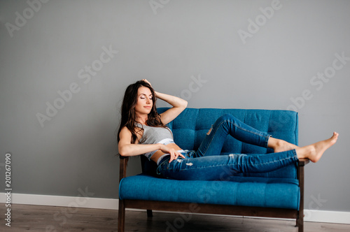 beautiful young girl lies on the sofa in blue jeans and a ...