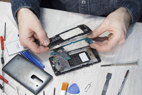 Obraz Naprawa telefonu komórkowego. Dłonie mężczyzny wyjmują płytkę z układem scalonym z obudowy telefonu komórkowego. - fototapety do salonu