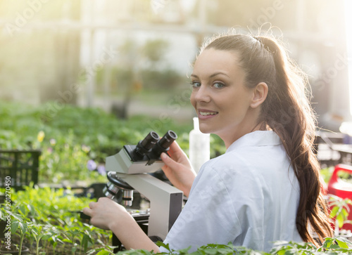 Photo Agronomist with microscope in greenhouse