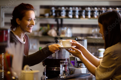 Young cafe manager and business woman in cafe