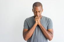 Calm Spiritual Handsome African Guy Praying With Closed Eyes. Serious Peaceful Young Man With Joining Hands Meditating. Belief Concept