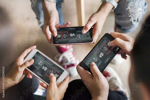 Group of diverse friends playing game on mobile phone Fototapet