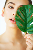 Skin Care. Green Leaf Shading a Half of Beautiful Woman Face. Beauty Treatment. Cosmetology. Beauty Spa Salon