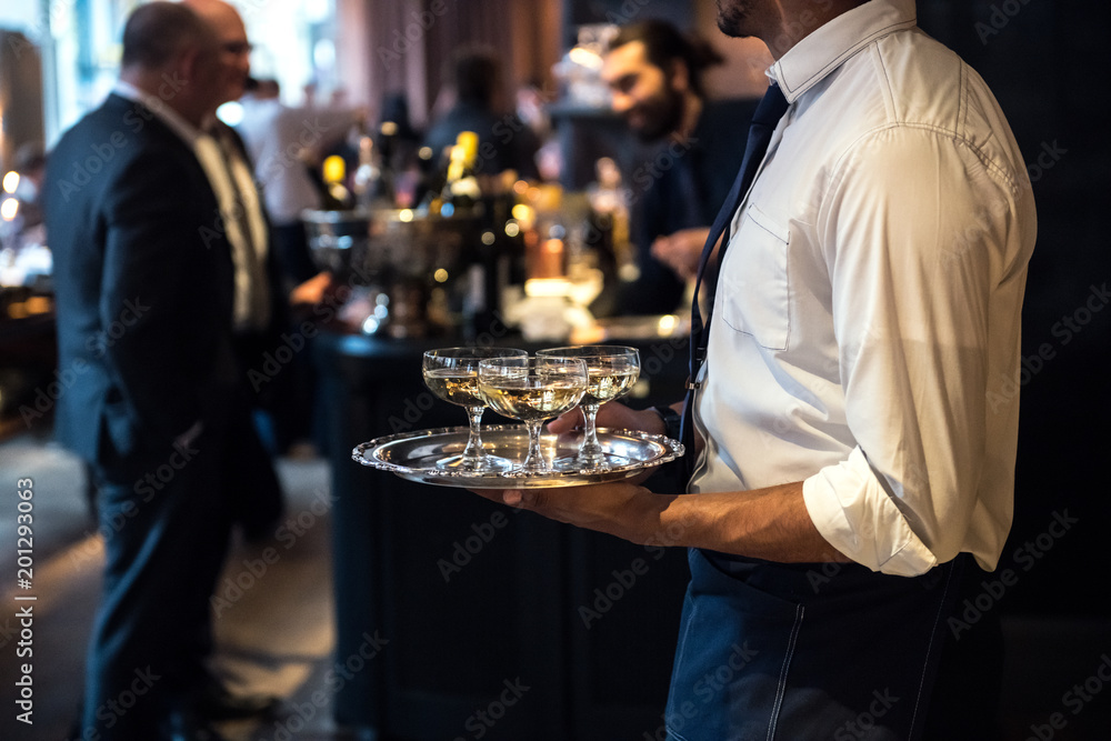 Fototapeta Waiter from catering service carrying champagne wine drinks on the event