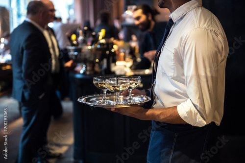 Fotografía  Waiter from catering service carrying champagne wine drinks on the event