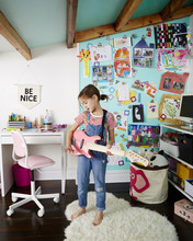 Girl In Kids' Playroom With Desk, Artwork Display And Pink Guitar
