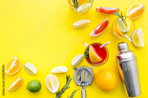 Deurstickers Bar Mix exotic fruit cocktail with alcohol. Shaker and strainer near citrus fruits and glass with cocktail on yellow background top view space for text