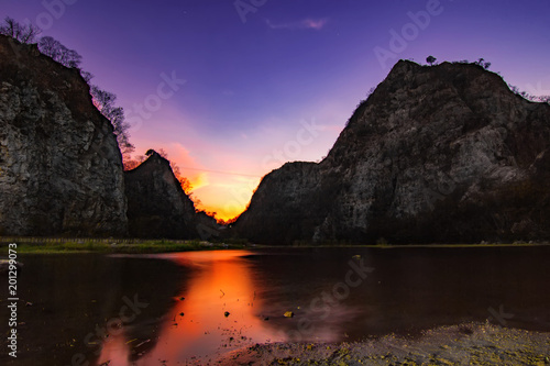 Deurstickers Zwart Twilight evening sunset cloudy sky reflect color on water lake with high rock cliff mountain background landscape