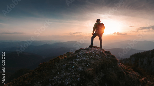 Slika na platnu Tourist man hiker on top of the mountain. Active life concept
