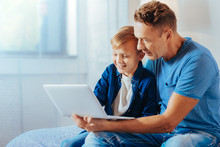 New Device. Cute Positive Happy Boy Smiling And Looking At The Netbook Screen While Sitting Together With His Father