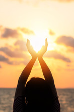June Summer Sun Solstice Concept And Silhouette Of Happy Young Woman's Hands Relaxing, Meditating And Holding Sunset Against Warm Golden Hour Sky On The Beach With Ocean Or Sea Background
