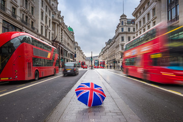 Fototapeta London, England - British umbrella at busy Regent Street with iconic red double-decker buses and black taxies on the move
